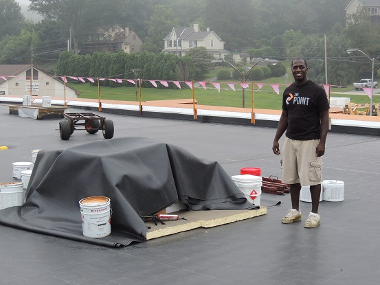 The Point's Executive Director Dwayne Walton shows off the youth center's new roof Saturday morning.