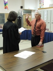 District Justice Nancy Gill administers the oath of office to returning board member Hank Oleyniczak.